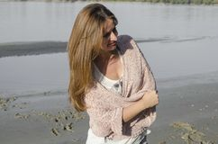 Young Woman Standing near the river. She is standing on sand beach Royalty Free Stock Photography