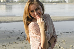 Young Woman Standing near the river. And smiling, she is standing on sand beach Stock Images