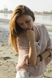 Young Woman Standing near the river. And smiling, she is standing on sand beach Royalty Free Stock Photo