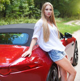 Young woman standing near a  sports car Stock Images