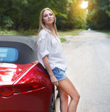 Young woman standing near a  sports car Royalty Free Stock Photography