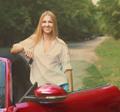 Young woman standing near a sports car holding keys. Beautiful blond young woman standing near a sports car holding keys Royalty Free Stock Photography