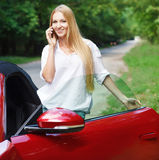 Young woman standing near a  sports car and talking by mobile ph Royalty Free Stock Image