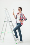 Young woman standing near the stepladder and holding a hammer Stock Photo