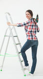 Young woman standing near the stepladder and holding a screwdriv Royalty Free Stock Photos