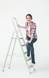 Young woman standing near the stepladder Royalty Free Stock Image