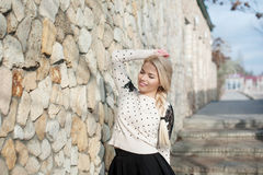 Young woman standing near the stone walls. Free Happy Woman Stock Image