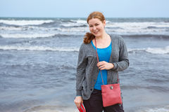 Young woman standing near stormy sea Stock Photos