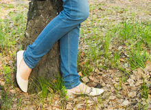 Young woman standing near a tree, legs, jeans, shoes closeup. Young woman standing near a tree, legs, jeans shoes closeup royalty free stock photo