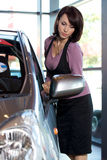 Young woman standing by new car in showroom Stock Image