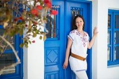 Young woman standing next to blue door Stock Photos