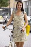 A young woman standing next to her bicycle Stock Photos