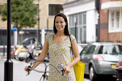 A young woman standing next to her bicycle Royalty Free Stock Photos