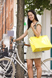 A young woman standing next to her bicycle, carrying a shopping bag Stock Photos