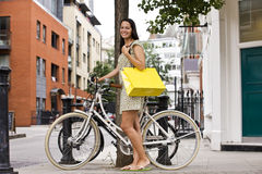 A young woman standing next to her bicycle, carrying a shopping bag Royalty Free Stock Photo