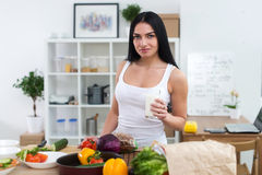 Young woman standing next to kitchen table with fresh vegetables drinking milk in the morning. Stock Images