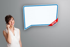 Young woman standing next to a modern speech bubble copy space a Royalty Free Stock Photography