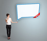 Young woman standing next to a modern speech bubble copy space a Stock Photos