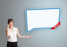 Young woman standing next to a modern speech bubble copy space a Royalty Free Stock Photo