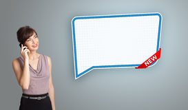 Young woman standing next to a modern speech bubble copy space a Stock Photography