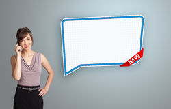 Young woman standing next to a modern speech bubble copy space a Royalty Free Stock Image