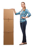 Young woman standing next to tower of boxes Royalty Free Stock Image