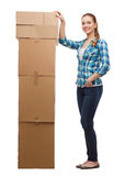 Young woman standing next to tower of boxes Royalty Free Stock Images