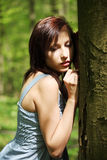 Young woman standing next to tree Stock Photo