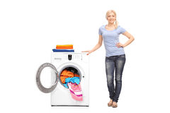 Young woman standing next to a washing machine Royalty Free Stock Photos
