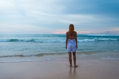 Young woman standing on ocean beach Stock Photo