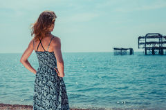 Young woman standing by the ocean with old pier Stock Images