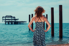 Young woman standing by the ocean with old pier Stock Photos