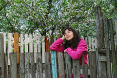Young woman standing by old fence and dreamy looking Royalty Free Stock Photography