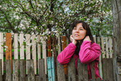 Young woman standing by old fence and dreamy looking Royalty Free Stock Image
