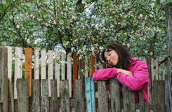 Young woman standing by old fence and smell garden fragrance Royalty Free Stock Photography