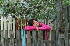 Young woman standing by old fence and yawn Royalty Free Stock Photo