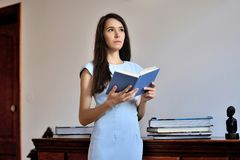 A young woman standing with an open book in her hands royalty free stock images