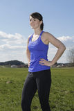 Young woman standing outdoors on a green field in workout clothe Stock Images