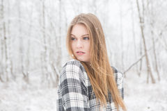 Young woman standing in outdoors in the snow. Young woman in black and white plaid shirt stading in a snow covered forrest Royalty Free Stock Image