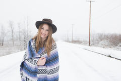 Young woman standing in outdoors in the snow. Young woman in the snow wearing a bohemian style blanket and hat during a winter storm Stock Photography