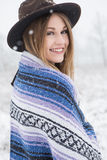 Young woman standing in outdoors in the snow. Young woman in the snow wearing a bohemian style blanket and hat during a winter storm Stock Images