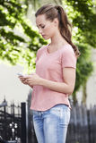 Young woman standing outdoors, texting Royalty Free Stock Image