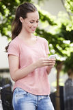 Young woman standing outdoors, texting Royalty Free Stock Photo