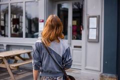 Young woman standing outside pub Stock Photos