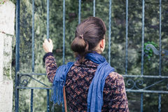 Young woman standing outside some gates Stock Photo