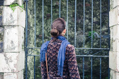 Young woman standing outside some gates Stock Images