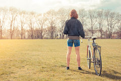 Young woman standing in park with bicycle Stock Image