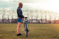 Young woman standing in park with bicycle Royalty Free Stock Image