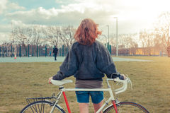 Young woman standing in park with bicycle Stock Photography