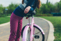 Young woman standing in park with bicycle Royalty Free Stock Photography